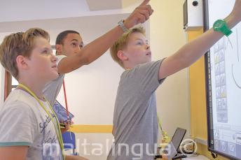 Leerkracht helpt studenten bij het interactief whiteboard
