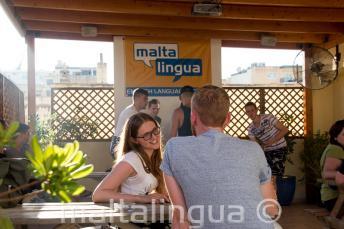 Engels student praten met haar leraar op het terras