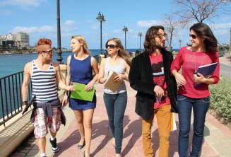 Studenten oefenen Engels na de les naast de St. Julians Bay, Malta