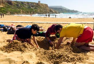 Groepsleider en studenten amuseren zich op het strand