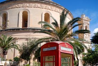 Een rode telefooncel in de voorkant van de Mosta Rotunda