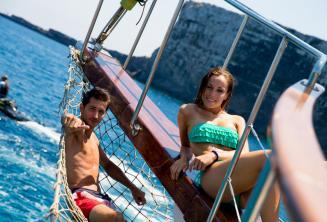 2 studenten loungen op het dek van een boot op Comino in Malta.