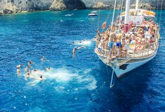 Taal studenten springen van een boot in Crystal Bay, Comino.