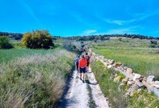 Een groep van het Engels leerlingen wandelen door het landschap in Malta